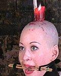 Glatzköpfige Sklavin mit Zungenpranger bekommt eine Jerze auf den Kopf, die ihr Gesicht volltropft und wachst