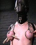 Süße Sklavin mit Latexleggins und kompletter Bondagemaske bekommt ihre Nippel am Halskorsett fixiert und wird ausgepeitscht